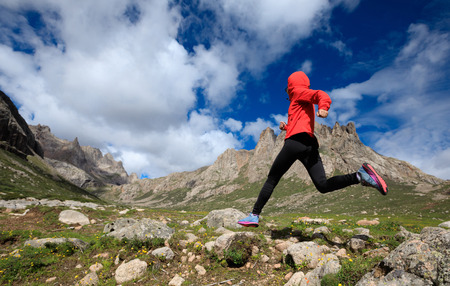 young woman trail runner jumping over stream water at mountain