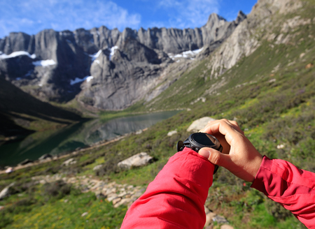 woman hiker checking the altitude with sports watch in mountains