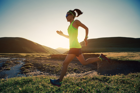 young fitness woman trail runner running in sunset grassland