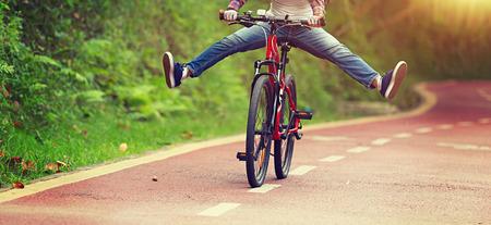 jonge vrouw fietser plezier fiets rijden op bospad Stockfoto