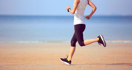 sporty woman runner running on seaside sandy beach