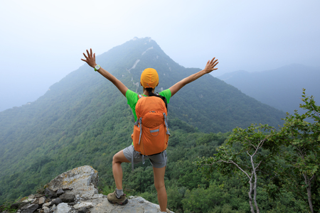 successful woman hiker open arms to the great wall on the top of mountain