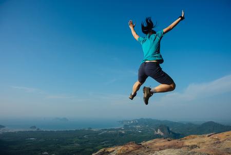 joyful woman hiker jumping on rocky mountain top Stock Photo