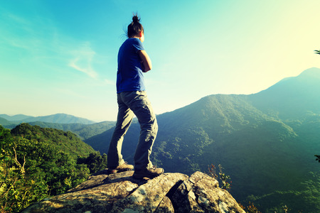 successful young woman enjoy the view on cliffs edge Stock Photo