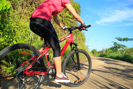woman cyclist cycling on forest trail