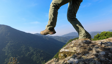 brave woman hiker walking to the cliff edge on top of mountain Stock Photo