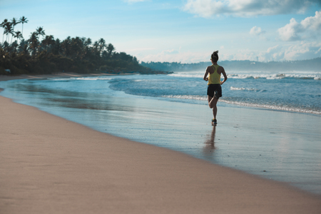 young fitness woman runner running on sandy beach Imagens - 89585757