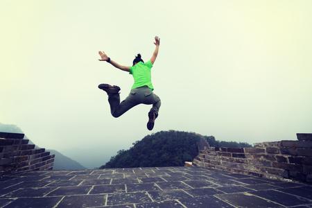 succesvolle vrouw wandelaar springen op grote muur