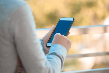 closeup of hands using smartphone outdoor