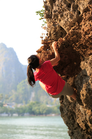 Young woman rock climber climbing on seaside cliff Stock Photo