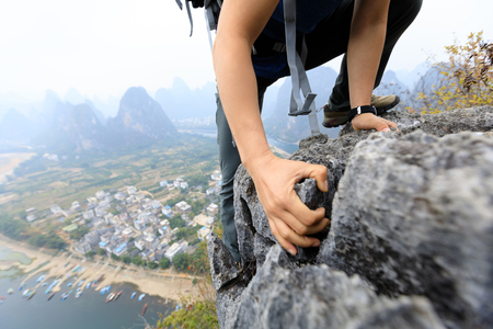 brave woman backpacker climbing rock on mountain top cliff edge