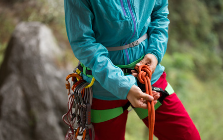 Сlimber wearing safety harness making a eight rope knot  Stock Photo