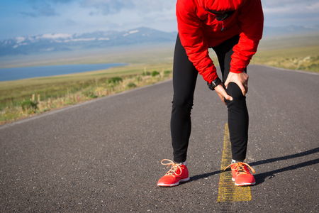 Fitness woman runner hold her sports injured leg on country road