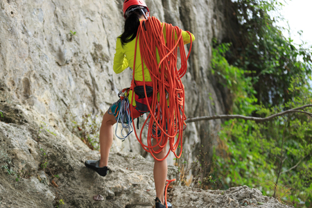rock climber standing with climbing gears and rope in front of mountain cliff outdoor