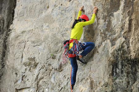 female rock climber climbing on mountain cliff