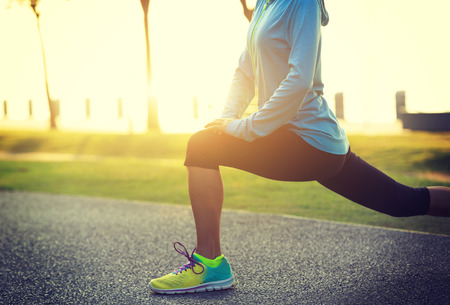Young fitness woman stretching legs before run at tropical park Stock Photo