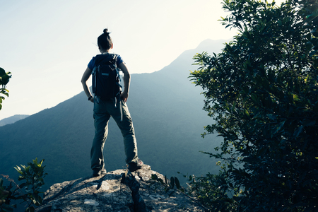 successful female backpacker enjoy the view cliff's edge Stock Photo