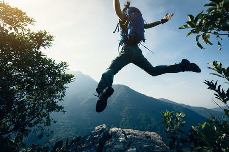 successful female backpacker jumping on cliff's edge