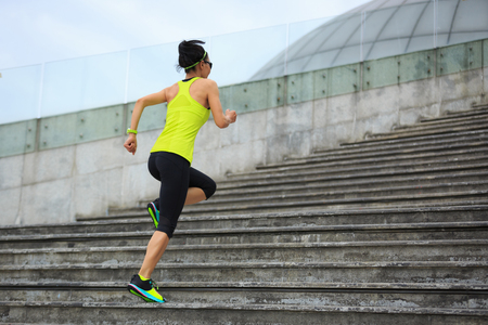 Young fitness sporty woman running upstairs