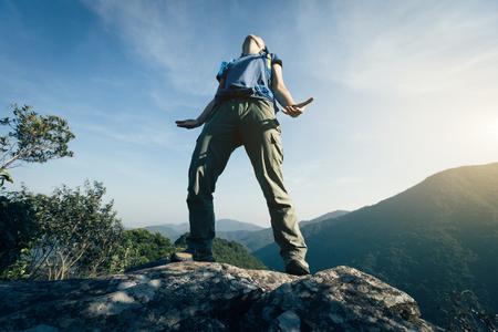 successful female backpacker breath the fresh air cliffs edge