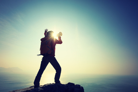 Young woman shouting with loudspeaker on windy sunrise coast cliff edge Standard-Bild