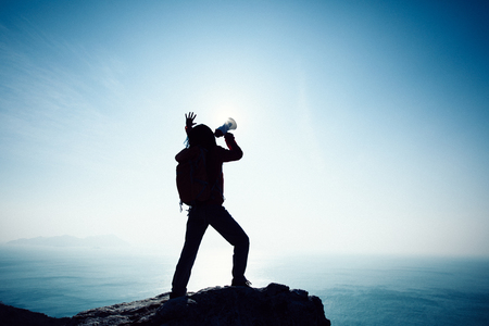 Young woman shouting with loudspeaker on windy sunrise coast cliff edge Foto de archivo