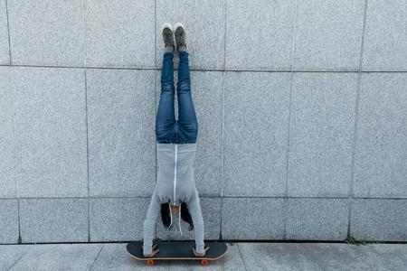 female skateboarder doing a hand on skateboard against wall