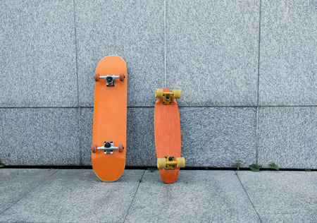 two skateboards against gray wall 写真素材