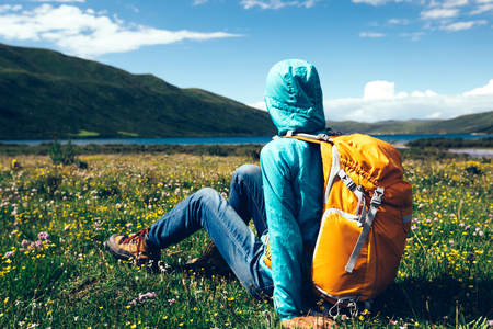 young backpacking woman sit on flowers and grass in high altitude mountains Stockfoto