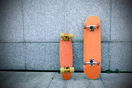 two skateboards against gray wall Stock Photo