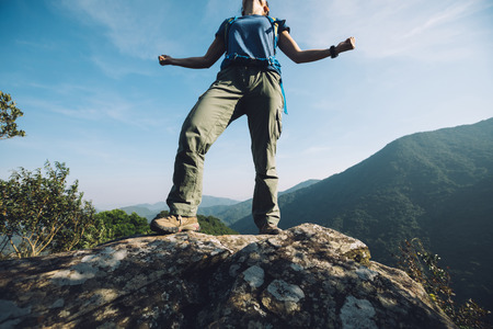successful female hiker standing on cliff's edge Stock Photo