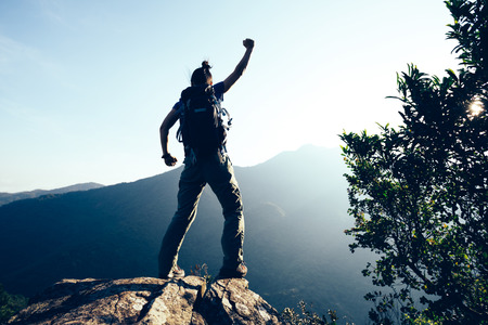 successful female hiker standing on cliffs edge Stock Photo