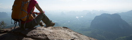 successful woman traveler sitting on mountain peak cliff edge