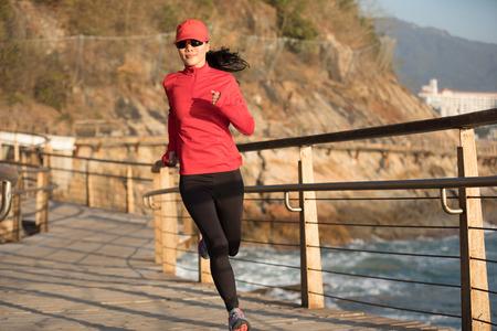 sporty fitness female runner running on seaside boardwalk Stock Photo