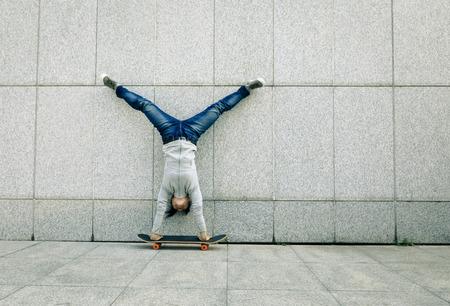 female skateboarder doing a handstand on skateboard against wall Stock Photo