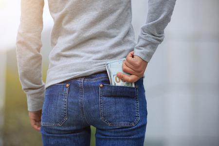 Female hand put money into pocket on blurred city background