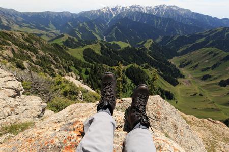 Hiker legs sit on mountain top cliff edge 스톡 콘텐츠