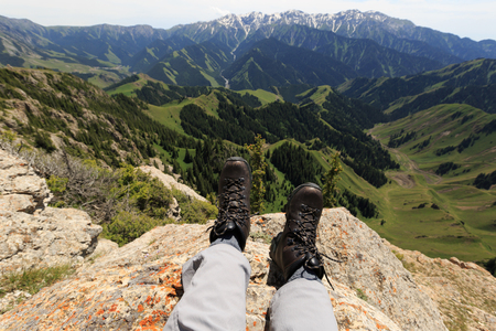 Hiker legs sit on mountain top cliff edge Фото со стока
