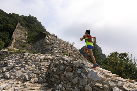 running woman trail runner on the great wall top of mountain