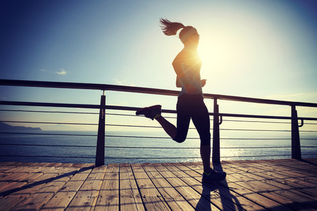 sporty fitness female runner running on seaside boardwalk during sunrise  Stock Photo