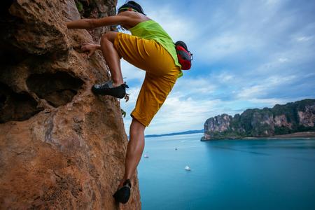 female rock climber climbing on seaside cliff
