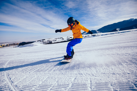 one woman snowboarder snowboarding in winter mountains