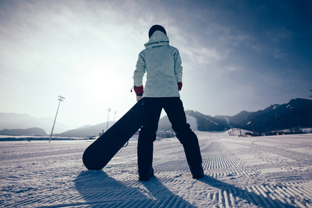 one snowboarder with snowboard looking at the snowobard piste in winter mountains