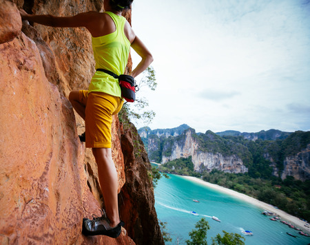 woman rock climber climbing on seaside cliff