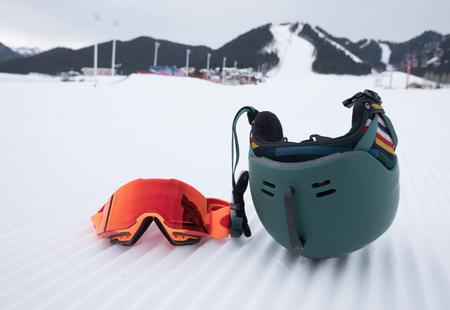 snowboard goggles and helmet on ski piste slop