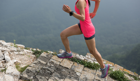 sporty fitness woman runner running upstairs on mountain top Stock Photo