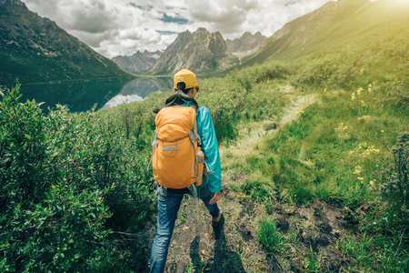woman hiker with  backpack hiking in mountains