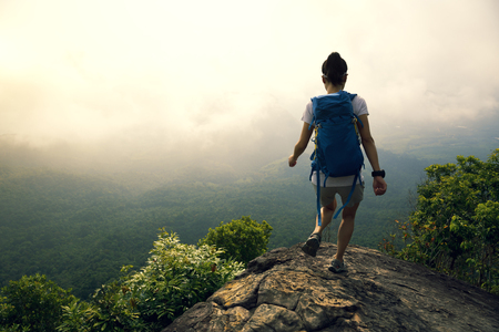 successful fitness woman running on the mountain top cliff edge 免版税图像