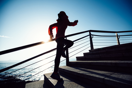 sporty fitness female runner running upstairs on coast trail Stock Photo