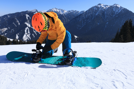One young woman snowboarder ready for snowboarding on winter mountain top